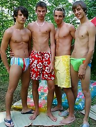 These four tanned twinks have found a quiet corner in the bushes and are busy sucking cock like they are icy poles.